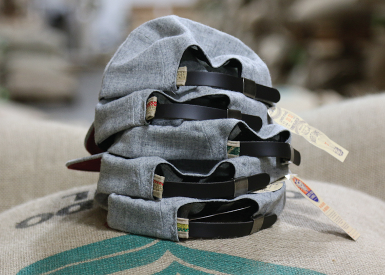 Each cap is tagged with a salvaged piece of burlap, all cut from the same Brazil Coffee Jute, and hand stitched to prevent from fraying.